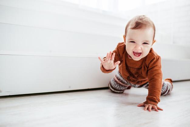 Noworodek śmieje się i raczkuje