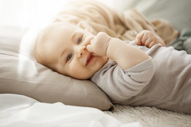 leżący i uśmiechający się niemowlak